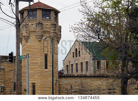 The hospital of the abandoned Illinois State Penitentiary, seen behind a guard tower and a wall topped with razor wire, in Joliet, Illinois.