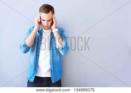 I need urgent help. Pleasant cheerless man holding his hands on the temples and having a headache while standing isolated on grey background