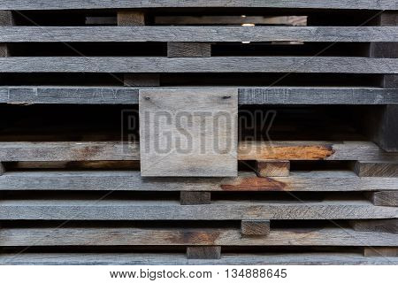 Oak planks for wine barrels stacked in piles for elution of tannins on the open air, with a blank plywood sign, on which can be located your text