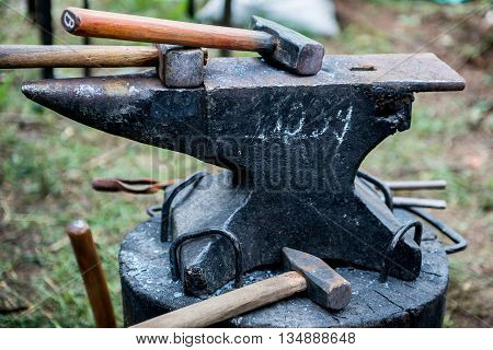 blacksmith works on an anvil. Master forges product. Tools and blacksmith anvil. Blacksmith working outdoors.