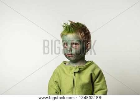 Sad little boy dressed as zombie on Halloween