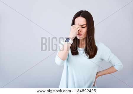 Unpleasant feelings. Cheerless sick woman feeling unhealthy and having a headache while standing isolated on white background
