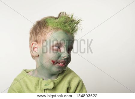 little boy dressed as a zombie on halloween looking right