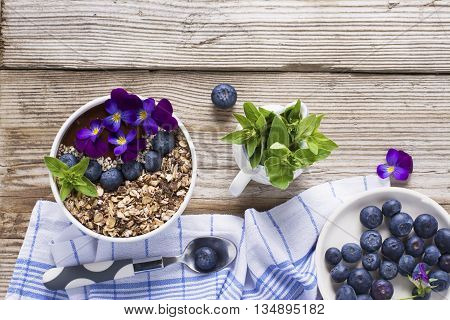 Chocolate Banana Smoothies Bowl with a topping of granola, blueberries, white sesame decorated with flowers purple garden viola on a simple wooden background. The concept of healthy organic breakfast snack.