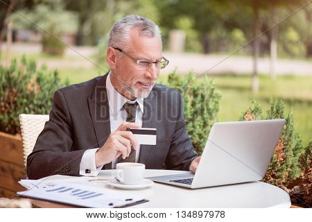 Pay it off online. Pleasant cheerful handsome senior man sitting at the table and holding credit card while using laptop