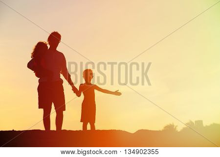 silhouette of father and two kids walking on beach at sunset