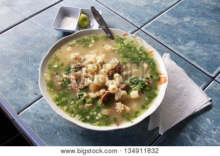 Bowl of sheep's head soup on restaurant counter in Peru