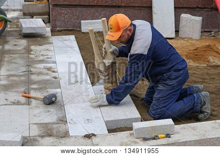 MOSCOW, RUSSIA - MAY 15, 2016: Work puts the big flagstones on the sidewalk. Reconstruction of the roadway within the city beautification program My Street in Moscow.