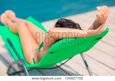 Attractive brunette on the beach. Young woman in swimwear laying in chair on the beach