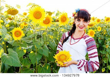 Beautiful smiling woman in national ukrainian blouse embrodery holding a sunflower on a field at backlight poster