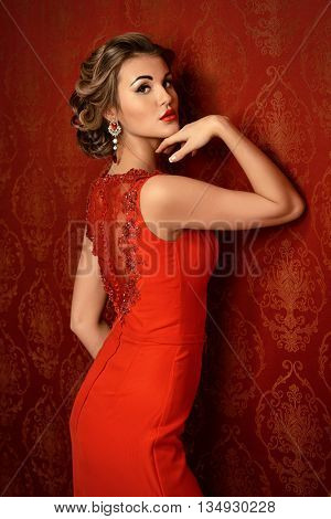 Portrait of a slender  elegant woman in beautiful red dress posing by vintage wallpaper. Luxury, rich lifestyle. Jewellery. Fashion shot.