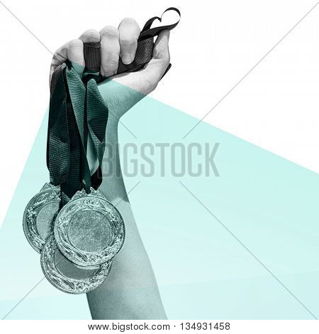 Hand holding three medals on white background against blue colors