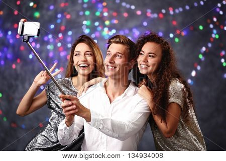 Young cheerful friends taking selfie on blurred colourful lights background