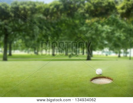 Golf ball at the edge of the hole on a sunny day at the golf course