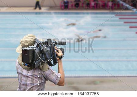 Video cameraman operator with competition swim pool in swimming stadium.