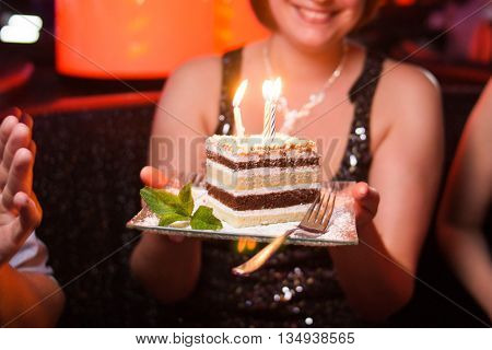 cake with candles on plate in womans hand-birthday party