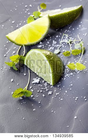 Lime wedges with sea salt and micro herbs, over dark slate.