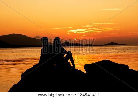 Silhouette of young couple in love at beachsunset background