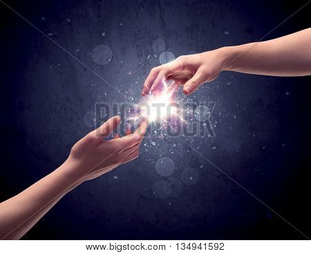 Two male hands reaching towards each other, almost touching with fingers, lighting spark in galaxy background concept poster