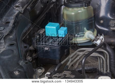 Close up of a fuse block and a power steering fluid reservoir