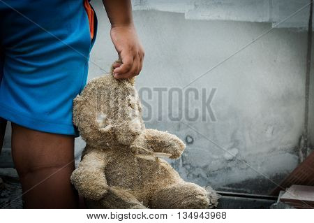 poor child holding a teddy bear vintage tone
