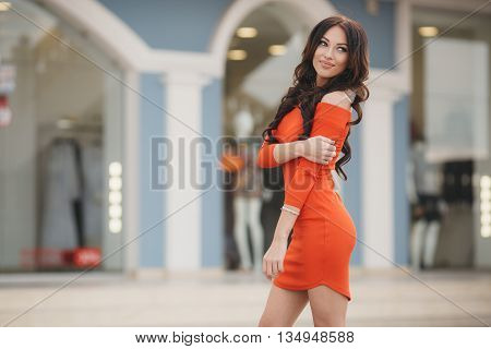 Summer portrait of a beautiful slim woman,brunette with long curly hair and grey eyes, dressed in a bright orange dress , wearing large black earrings, a cute smile posing outdoors in the city in the summer