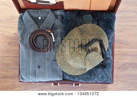 Vintage travel background. Top view of old suitcase with clothes on wooden floor. Retro style.