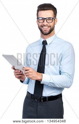 How may I help you? Confident young handsome man in shirt and tie holding digital tablet and looking at camera with smile while standing against white background