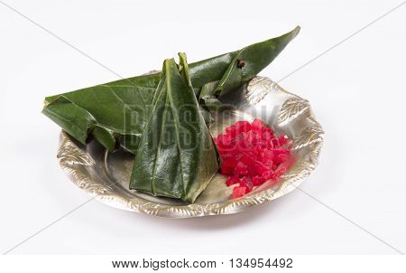 indian traditional masala paan or masala pan, masala meetha paan, beeda or digestive supplement after meals, in a decorative silver bowl with fresh red cherries and toothpick, top view