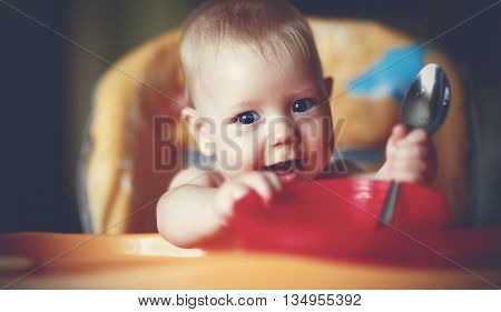 a  Happy baby boy spoon eats itself