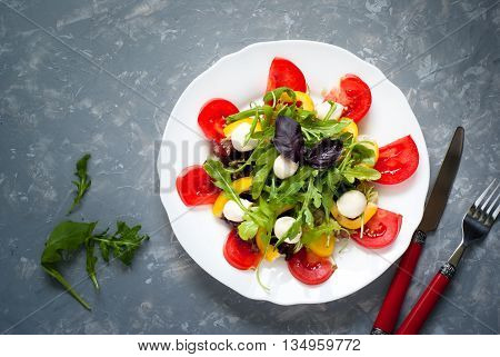 Fresh summer salad. Salad from tomatoes agaricus lettuce pepper and mozzarella. Grey beton background.