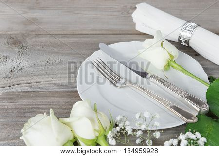 Beautiful decorated table with white plates linen napkin cutlery and white rose flowers on an old wooden table