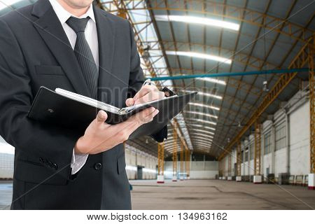 Professional businessman evaluation factory with blurred construction factory building site background industrial business concept