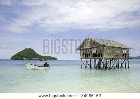 Dive Boat and Water Hut with View of Kri Island and Dampier Strait. Raja Ampat Indonesia
