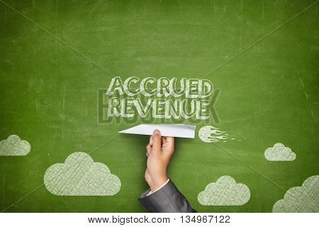 Accrued revenue concept on black blackboard with businessman hand holding paper plane