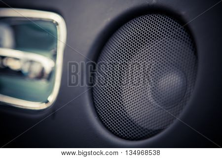 Close up shot of a round speaker in a car.