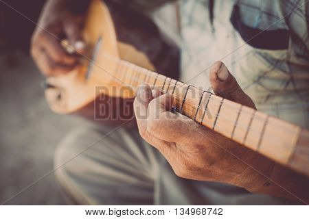 Close up shot of a man playing a Tatar instrument called