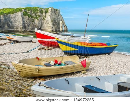 White cliffs of Etretat and colorful fishing boats ashore of English Channel. Etretat, France