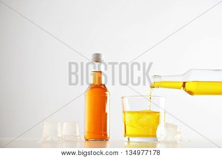 Yellow tasty lemonade drink pours from bottle to glass with ice cubes near closed sealed unlabeled bottle with orange beverage, isolated on white