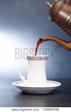 Black coffee flowing from vintage brass coffeepot into cup