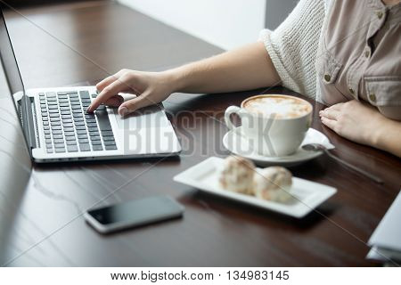 Close-up Of Female Hands Working On Laptop In Cafe