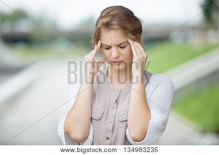 Portrait Of Stressed Woman With Headache Outdoors