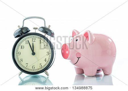 Alarm clock with piggybank on white background