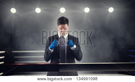 confident young businessman clenches wrapped fists in boxing ring in front of back lights