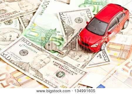 Toy car key and money over white. Rent buy or insurance car concept