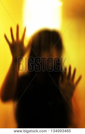 Horror woman behind the matte glass. Blurry hand and body figure abstraction.