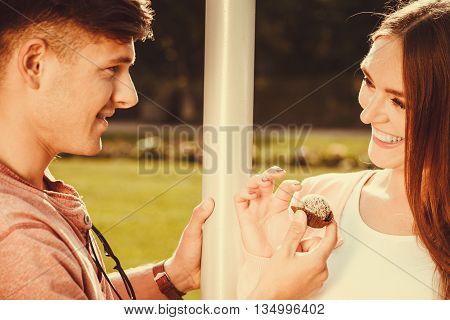 Love and dating. Young handsome man flirting with attractive woman by cupcake cookie. Happy cute lovers on date outdoor.