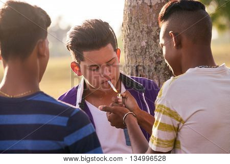 Youth culture young people group of male friends mixed race teen outdoor teenager in park. Hispanic kid smoking cigarette confident boy smoker. Health problems social issues.