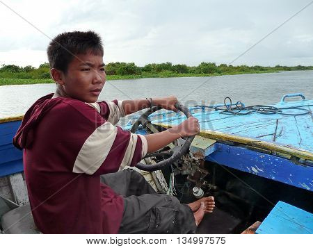 TONLE SAP LAKE, CAMBODIA - CIRCA OCT 2008 : A school boy drives a boat with merely functioning motor for tourists for few dollars to support family.