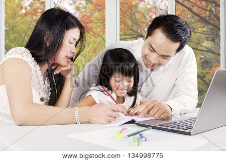 Happy Asian parents and their daughter doing schoolwork while writing on the book and using notebook computer at home